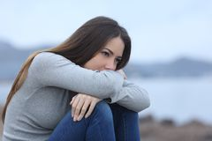 Sad girl looking away alone on the beach stock photography
