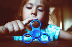 Funny little girl with a blue spinner Royalty Free Stock Photo