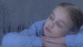Sad girl looking in window on rain drops, dreaming about family in orphanage. Stock footage stock video footage