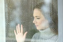 Sad girl looking through a window in a rainy day. Portrait of a sad girl looking through a window in a rainy day at home royalty free stock image