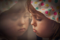 Sad girl looking through the window. Window reflection of a little sad baby girl royalty free stock photos
