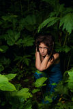 Sad girl lost in dark forest Royalty Free Stock Photo