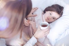 Sad girl lying in the bed while feeling unwell. Do not be so serious. Kind brunette female sitting near her child while giving cup with tea to make her feel Stock Images