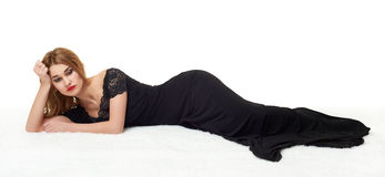 Sad girl lying on fur, dressed in black gown. Royalty Free Stock Photo