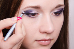 Sad girl makeup artist draws arrows Royalty Free Stock Images