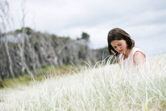 Sad girl in nature. Portrait of sad young girl on the beach. She is lost in her thoughts and looks unhappy Stock Photo