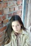 Sad girl near brick wall. Sad young girl with long hair near red brick wall Royalty Free Stock Photo