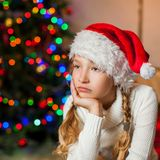 Sad girl near christmas tree at home Stock Image