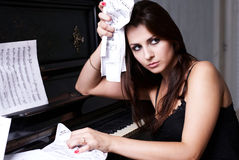 Sad girl near piano Royalty Free Stock Images
