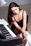 Sad girl near piano Stock Photo