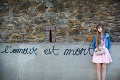 Sad girl near the wall with words Royalty Free Stock Photos
