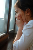 Sad girl near a window Royalty Free Stock Image