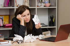 Sad girl in the office holds a crumpled sheet of paper Royalty Free Stock Image