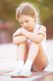 Sad girl outdoors. Lonely girl in elementary school age crying and feeling confused outdoors Stock Images