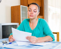 Sad girl with papers. Sad young girl with papers sits at the table in the room Royalty Free Stock Images