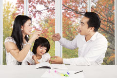 Sad girl with parents quarreling. Little girl crying while studying with her parents quarreling at home Stock Photography