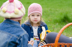 The sad girl at a picnic eats banana Royalty Free Stock Photo
