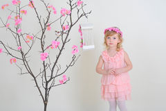 Sad girl in a pink dress against a tree. Sad girl in a pink dress near a flowering tree with a bird that flew out of the cell Royalty Free Stock Photography