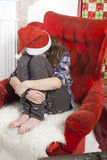 Sad girl in plaid shirt and a cap of Santa Claus sitting on a chair. Santa Claus did not bring gifts. Royalty Free Stock Images
