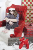 Sad girl in a plaid shirt and cap of Santa Claus sitting on a chair. Santa Claus did not bring gifts. Stock Images