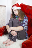 Sad girl in a plaid shirt and cap of Santa Claus sitting on a chair. Santa Claus did not bring gifts. Stock Image