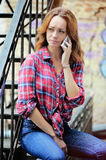 Sad girl in a plaid shirt talking on the phone. Angry girl in a plaid shirt talking on the phone. The concept of a lie Stock Photo