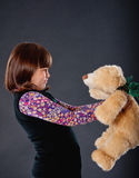 Sad girl playing with a teddy bear. Cheerful girl playing with his teddy bear on dark background royalty free stock images