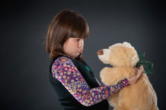 Sad girl playing with a teddy bear. Cheerful girl playing with his teddy bear on dark background stock photo