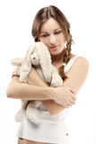 The sad girl with a plush hare Stock Images