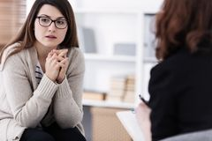 Sad girl with psychotherapist. Women`s issues support group concept stock photos