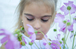 Sad girl and purple flowers. Sad young girl with eyes closed, blooming purple flowers in foreground Stock Image