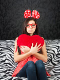 Sad girl with a red heart cushion. Sad girl with a big hair bow and a heart cushion sitting on the sofa and looking at camera stock images