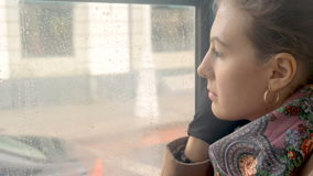 A sad girl rides a tram and looks out the window close-up. A beautiful girl with sad eyes rides in a tram. It is raining outside. She`s in a bad mood, she`s sad stock video