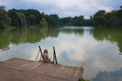 Sad girl on a river bank Royalty Free Stock Photo