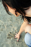 Sad girl on sand beach. Girl in depresion. Sad girl on drawing in sand royalty free stock image