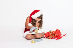 Sad girl in Santa Claus costume with inappropriate gift. Sad little girl in Santa Claus costume with her hand supporting her chin is holding inappropriate gift stock photos