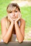 Sad girl sits on bench Stock Photo