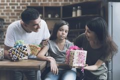 A sad girl sits on a chair, and a cheerful man and woman chew her with gifts for her. Parents obtspil sad girl who sits on a chair next to them and happily Stock Images