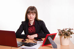 Sad girl sits at office table Stock Photo