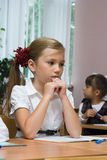 The sad girl sits at a school desk. Children at school at a lesson. The thoughtful girl sits at a school desk Royalty Free Stock Photos