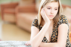 Sad girl sits at table Stock Photos
