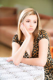 Sad girl sits at table Royalty Free Stock Photo