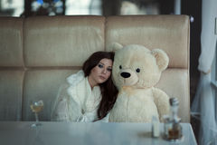 The sad girl sits at a table with toy bear. Stock Images