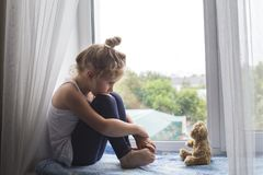 Sad litttle girl sits on a window sill and looks at a bear stock images