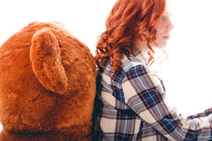 Sad girl sitting against the bear in despair. Isolated over white background Royalty Free Stock Image