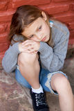 Sad girl sitting against the wall Royalty Free Stock Images