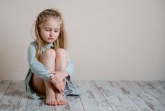 Sad girl sitting alone on the floor. Little sad girl in grey dress sitting alone on the floor and hugging her knees royalty free stock photo