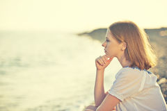 Sad girl sitting on the  beach and looks into the distance at se. Sad girl sitting on the coast on beach and looks into the distance at sea Royalty Free Stock Image