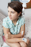 Sad girl sitting on bed in hospital Royalty Free Stock Photos