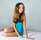 Sad girl sitting on the bed and looking away. square Stock Photos